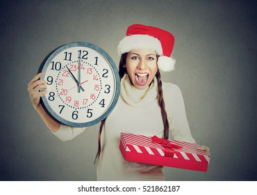 In a hurry young happy woman wearing red santa claus hat holding clock gift box isolated gray background. Emotion, funny face expression, last minute christmas shopping