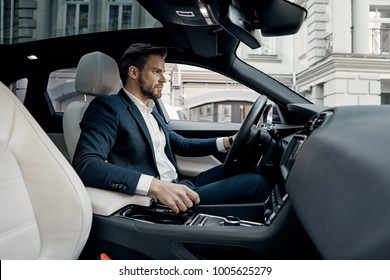 Hurrying to get things done. Handsome young man in full suit looking straight while driving a car