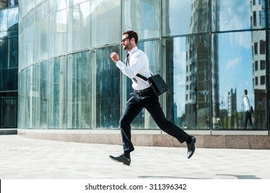 Hurrying to work. Full length of young businessman looking forward while running along the street