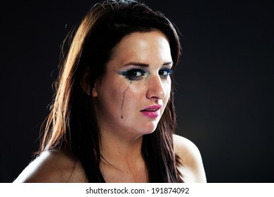 Hurt woman crying, face with smeared make up on dark background