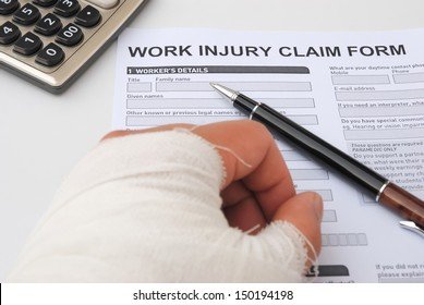 hurted hand and work injury claim form with pen & calculator, medical and insurance concept