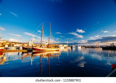Husavik, Iceland - August 17, 2017: Beautiful view of the historic town of Husavik with traditional houses and traditional fisherman boats lying in the harbor, northern coast of Iceland