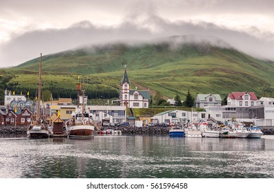 Husavik, Iceland - Fishing boats moored at harbour in subdued li