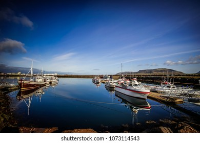 Husavik, Iceland - September 13, 2017: Beautiful view of the historic town of Husavik with traditional houses and traditional fisherman boats lying in the harbor, northern coast of Iceland