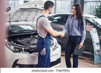 husband car mechanic and woman customer make an agreement on the repair of the car.