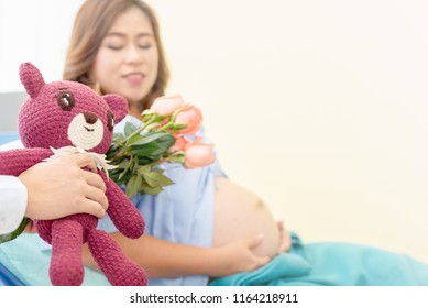 Husband gives the present to pregnant wife in the hospital.  Friend offer the flower and lovey doll to pregnant for encouragement.