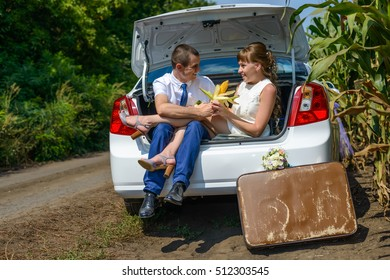 Husband giving wife an ear of corn while in open trunk lid of automobile. Brown suitcase and bouquet on ground.