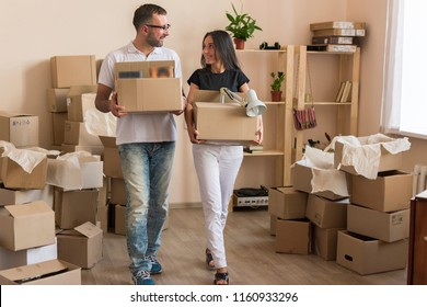 Husband with glasses and a white t-shirt hugs a young dark-haired wife. Couple sitting on the floor in front of shelves with things. A lot of boxes in front of the pair and around. Moving young family