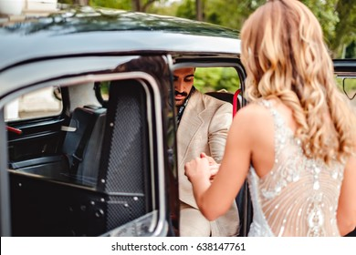 Husband helping bride to enter the car on their wedding day