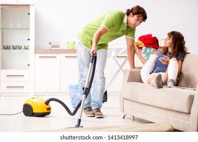 Husband helping leg injured wife in housework