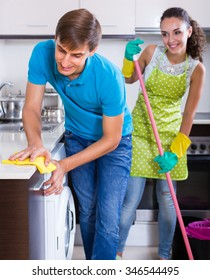 Husband helping smiling young housewife doing regular clean up at kitchen