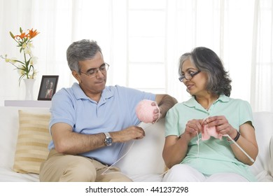 Husband helping while his wife is knitting