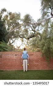 Husband helping wife see over brick wall