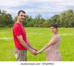 Husband with his pregnant wife on the green meadows