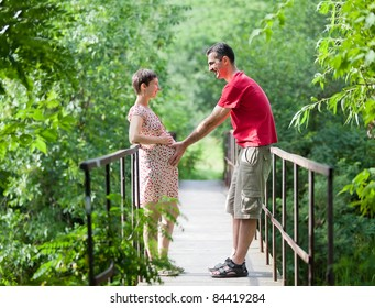 Husband with his wife on the bridge in green forest