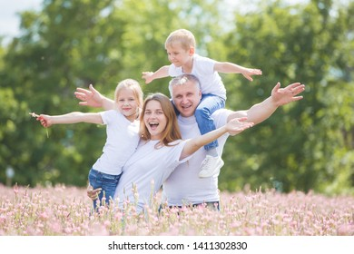 A husband with his wife and two children play in a field of pink flowers. Man, woman and children are wearing white T-shirts and jeans.