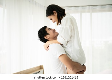Husband holding his wife up and kiss in bedroom, concept of couple and relationship.  Couple in Valentine day.