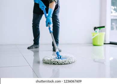 Husband housekeeping and cleaning concept, Happy young man in blue rubber gloves wiping dust using mop while cleaning on floor at home.