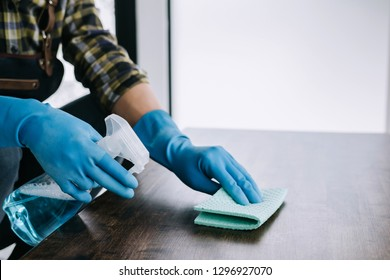 Husband housekeeping and cleaning concept, Happy young man wiping dust using a spray and a duster while cleaning on table at home.