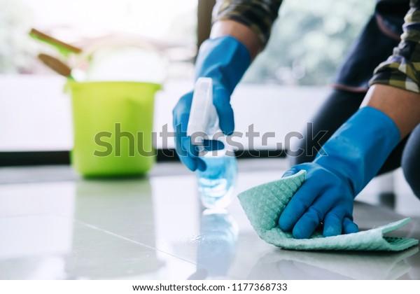 Chồng vệ sinh và làm sạch khái niệm, người đàn ông trẻ hạnh phúc trong găng tay cao su màu xanh lau bụi bằng cách sử dụng một bình xịt và một bụi trong khi làm sạch trên sàn nhà ở nhà.
