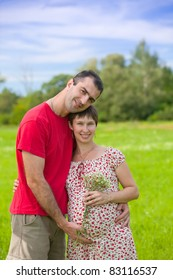 Husband hugs his pregnant wife outdoor