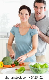 Husband massaging his wife while she's cutting vegetables in a kitchen