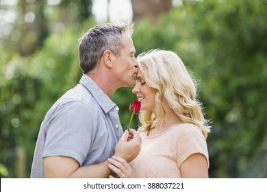 Husband offering a rose to wife outside in the forest