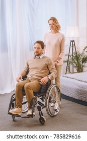 husband on wheelchair and wife looking away in bedroom