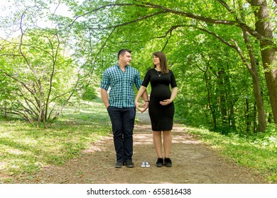 Husband with a pregnant woman in the forest