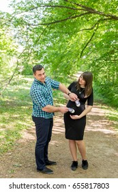 Husband with a pregnant woman in the forest and sneakers