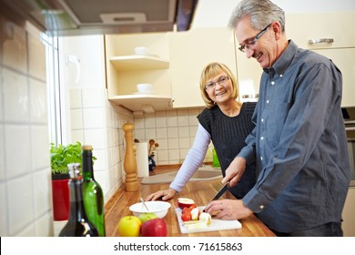 Husband preparing fruits for granola in the kitchen while wife is watching