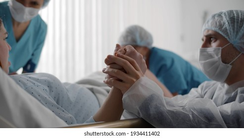 Husband in protective mask comforting pregnant woman during labor in ward of hospital. Young woman pushing giving birth in clinic delivery room with doctors and husband