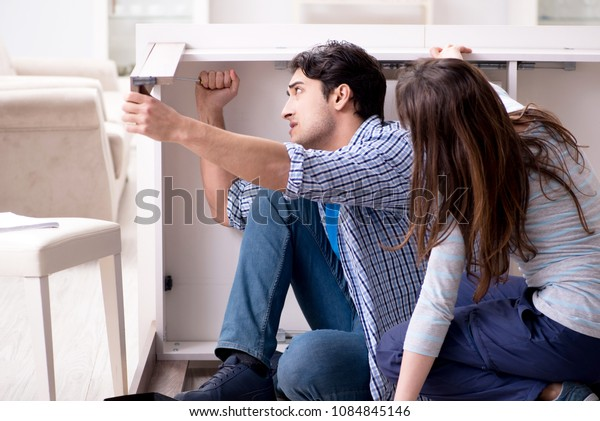 Husband repairing broken table at home