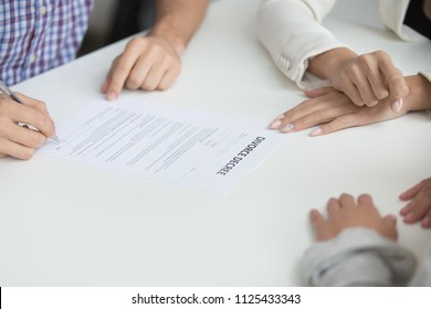 Husband signing uncontested divorce decree paper giving permission to break up, unhappy couple get divorced in lawyers office, marriage dissolution concept, close up view of hand putting signature