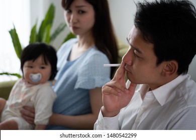 Husband smoking cigarette beside wife and baby