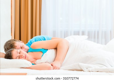 husband tenderly embracing his beloved wife in bed