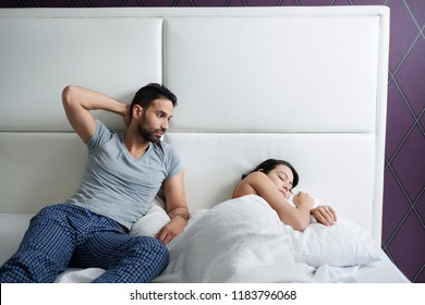 Husband trying sexual approach to bored wife in bed. Upset woman refusing to have sex with man and going back to sleep. Relationship problems for married people at home