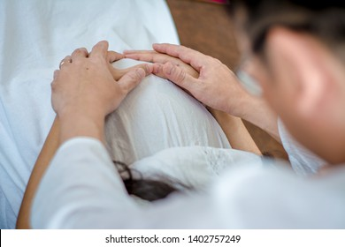 Husband uses hand to touch belly of pregnant wife in white dress, with soft sunlight In morning relaxed atmosphere,concept pregnancy birth of new mother,including preparation before birth,