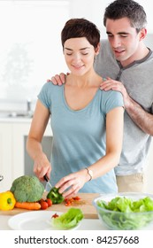 Husband watching his wife cutting vegetables in a kitchen