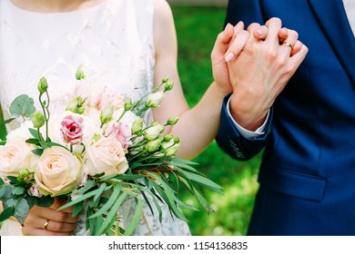 Husband and wife in blue suit and wedding dress getting married and holding hands
