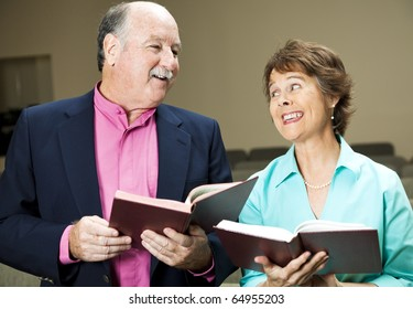 Husband and wife in church, singing hymns.