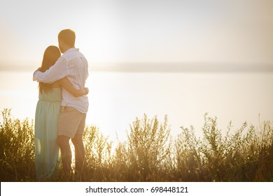 Husband and wife embrace against the background of nature, loving couple spend a romantic day together, the man gently brushed the woman by the shoulder, they look to the distance
