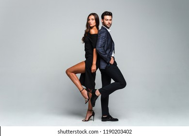 Husband and wife. Full length of young beautiful couple bonding back to back and looking at camera while standing against white background