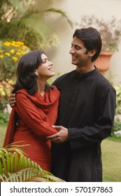 husband and wife in garden embracing, smiling at each other