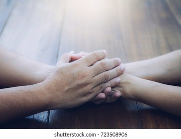 husband and wife join hands and  pray  together on wooden table with the light from above with copy space fro your text.