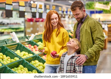 husband and wife with a kid buy fruits, apples. family of three choosing fresh apple in fruits department of supermarket or market