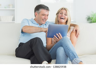 Husband and wife laughing at tablet pc on the sofa