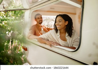 Husband and wife looks out of rv window, trailer