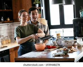 Husband and wife making pancakes at home. Loving couple having fun while cooking.