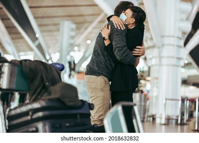 Husband and wife meeting after long separation during covid-19 outbreak at airport arrival gate. Female with face mask welcoming male traveler at airport arrival.